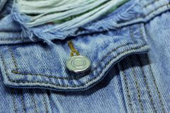Denim jacket pocket with metal button and fashionable fringes. Close-up Royalty Free Stock Photography