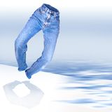 Denim jeans. A heel clicking womens form fitted worn denim jeans over a water gradient into white background Royalty Free Stock Photography