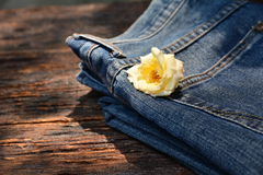 Denim jeans, Denim jeans with white flower. On wooden background Stock Photography