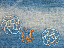 Denim jeans embroidered flowers texture background Stock Photo