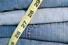 Denim Jeans measuring tape. Stack of denim jeans with cloth measuring tape Royalty Free Stock Image