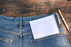 Denim jeans texture, Denim jeans with notebook and pen on wooden Royalty Free Stock Photo