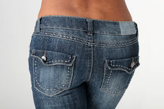 Denim Model. Portrait of a young african american woman modeling blue denim jeans. This view is from the back side of her royalty free stock photography