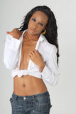 Denim Model. Portrait of a young african american woman modeling blue denim jeans and a white shirt that is unbuttoned royalty free stock photo