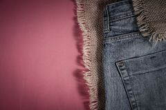 Denim pants are on the background of old linen burlap stock photos