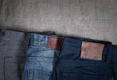 Denim pants of different colors lie on old linen burlap abstract background royalty free stock photo
