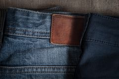 denim pants of different colors lie on old linen burlap abstract background stock photography