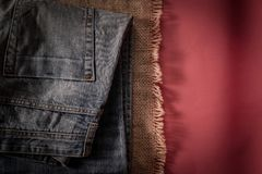 Denim pants are on the background of old linen burlap royalty free stock photos