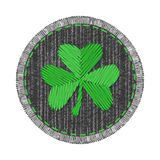 Denim patch with shamrock. Black round denim patch with green shamrock embroidery, stitch and fringe. Jeans fabric with Irish symbol of Saint Patricks Day Stock Photo