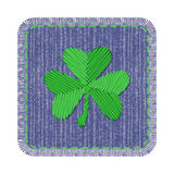 Denim patch with shamrock. Blue rectangle denim patch with green shamrock embroidery, stitch and fringe. Square jeans fabric with Irish symbol of Saint Patricks Royalty Free Stock Photo