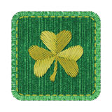 Denim patch with shamrock. Green rectangle denim patch with golden shamrock embroidery, stitch and fringe. Square jeans fabric with Irish symbol of Saint Royalty Free Stock Images