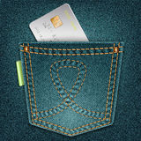 Denim pocket with credit card on a gray background. Royalty Free Stock Image