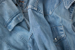 Denim shirt details. Closeup of denim shirts with focus on sleeves from above in studio shot Royalty Free Stock Photography