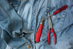 Denim shirts and hand tools. Closeup of denim shirts and hand tools lying on them Stock Image