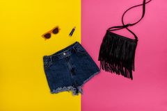 Denim shorts, black handbag, lipstick and glasses. Bright yellow and pink background. Fashionable concept Stock Image