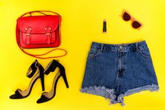 Denim shorts, black shoes, red handbag and glasses. Bright yellow background. Fashionable concept Royalty Free Stock Photo