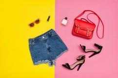 Denim shorts,black shoes, red handbag, sunglasses. Bright yellow. Denim shorts, black shoes, red handbag, sunglasses. Bright yellow and pink background Stock Image