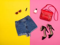 Denim shorts, shoes and a red handbag, bright yellow and pink background. Fashionable concept Royalty Free Stock Photo