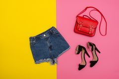 Denim shorts, shoes and a red handbag, bright yellow and pink background. Fashionable concept Stock Photos