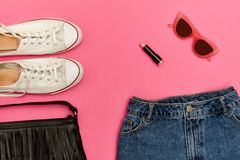 Denim shorts, white sneakers, black handbag, lipstick and glasses. Bright pink background. Fashionable concept Royalty Free Stock Image