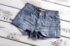 Denim shorts on wooden shelf. Royalty Free Stock Image