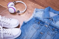 Denim sleeveless, sneakers and headphones. Summer dress with sleeveless and light shoes Royalty Free Stock Images