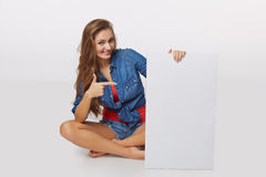 Denim style portrait of teen girl on the floor holding white bla Stock Photos