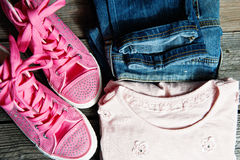 Denim trousers with light top and pink canvas shoes. Light denim shorts on table. Stock Images