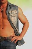 Denim vest. Male torso in denim vest wearing a cross jeans and belt Royalty Free Stock Photo