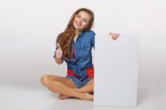 Denimartporträt des jugendlich Mädchens auf dem Boden, der weißes bla hält stockfotografie