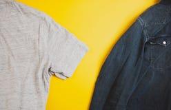 Denimjasje en grijze t-shirt aan twee kanten van de foto, op gele achtergrond, met copyspace royalty-vrije stock afbeeldingen