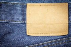 Denimjeans-Gewebebeschaffenheit oder Denimjeanshintergrund mit leerem ledernem Aufkleber Lizenzfreie Stockfotos