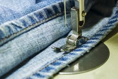 Denimstof op de naaimachine Close-up van het naaien proce Stock Afbeelding