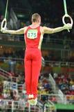 Denis Abliazin van Russische Federatie concurreert bij Def. van Mensen` s Ringen op de artistieke gymnastiekconcurrentie bij het  stock afbeeldingen
