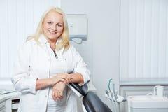Denist supérieur dans sa pratique dentaire photographie stock libre de droits