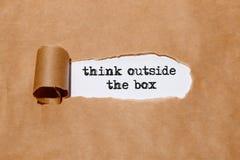 ` Denk buiten het vakje ` dat door schrijfmachine achter gescheurd document wordt geschreven royalty-vrije stock fotografie
