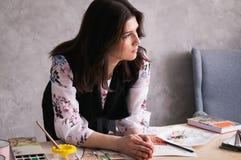 Denken: der weibliche Designer lehnte ihre Ellbögen auf dem Tisch und erwog Auf dem Tisch unvorsichtig zerstreute Skizzen, Farben stockbild