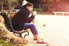 Denken, durchdachter gutaussehender Mann auf der Bank draußen Stockfotografie