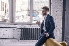 Denken an etwas Durchdachter junger Mann in der vollen Klage und Sonnenbrille trinkt Whisky und das Schauen, weghalten Hand auf stockfotos