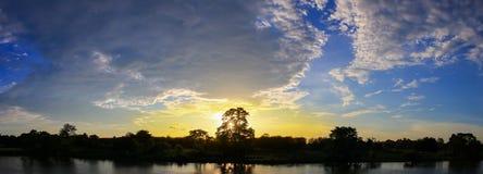 Denken het mooie kleurrijke landschap van de panoramazonsondergang en de de bergrivier van de silhouetboom in de tijd van de heme Stock Afbeelding