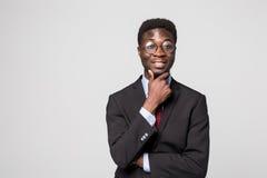 Denken an neue Lösungen Hübscher junger afrikanischer Mann, der Hand auf Kinn hält und auf Kamera mit Lächeln auf Grau schaut stockbild
