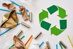 Denken Sie an Ökologie Zerknittern Sie Papier, Plastik und Batterien nahe Recycling-Symbol lizenzfreies stockbild