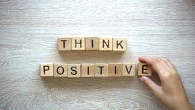 Denken Sie Positiv, die Frau, die Phrase von den hölzernen Würfeln machen, Motivation und Inspiration stockfotos