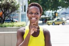 Denkend Afrikaans Amerikaans meisje met geel overhemd en kort haar Royalty-vrije Stock Foto's