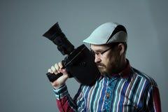 Denkende alte Retro- Filmkamera des bärtigen Mannes Lizenzfreies Stockfoto