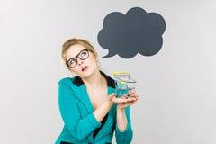 Denkende bedrijfsvrouw die klein uiterst klein boodschappenwagentje houden royalty-vrije stock afbeeldingen