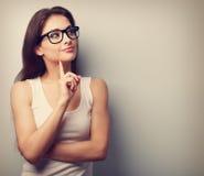 Denkende Berufsfrau in den Gläsern, die mit dem Finger darunter schauen Lizenzfreies Stockbild