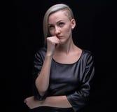 Denkende blonde Frau im ledernen Kleid Lizenzfreies Stockfoto