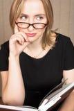 Denkende blonde Frau und Buch Stockfoto