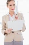 Denkende blonde Geschäftsfrau, die Klemmbrett hält Lizenzfreie Stockfotografie